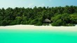 tropical island shore with white sand beach and bungalow with palms in the background drone aerial footage thailand