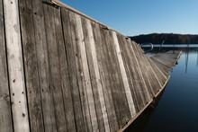 A Damaged Wood Pier On A Lake.