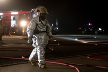 Firefighters In Silver Suit Operating On Airport Site At Night.