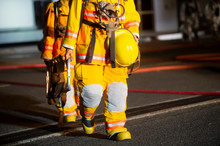 Firefighters In Yellow Suit With Oxygen Mask Walking On Airport Site At Night.