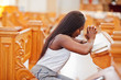 canvas print picture - African american woman praying in the church. Believers meditates in the cathedral and spiritual time of prayer. Afro girl folded hands while sitting on bench.
