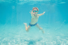 Boy Having Fun Playing Underwater In Swimming Pool On Summer Vacation