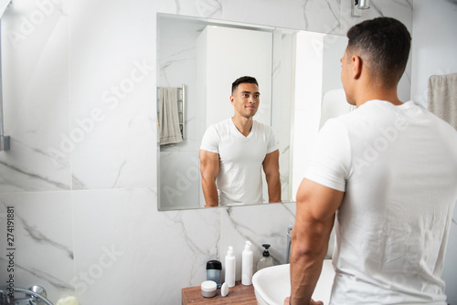 Obraz Back side of smiling young man looking at mirror - fototapety do salonu