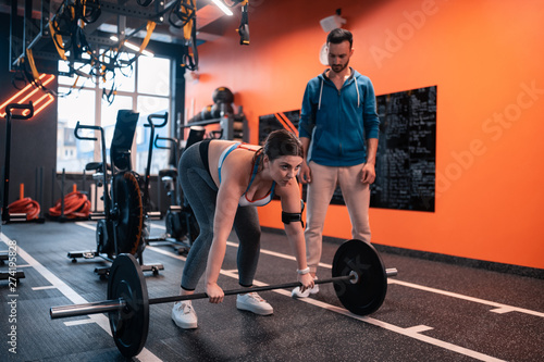Fotografija  Dark-haired plump woman trying to lift barbell for the first time