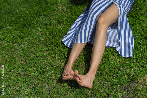Poster Individuel Young lady with bare feet lying on green grass