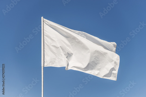 Photo  White flag against the blue sky