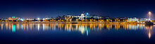 Panoramic View At Night Of Cagliari Skyline Reflected On The Calm Sea With The Church Of Bonaria In First Place.