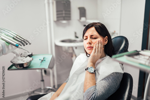 Fotografia  Woman with toothache at dentist office.