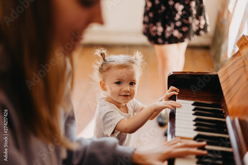 Cute little happy child girl playing piano in a light room. Selective focus, noise effect - 274217426