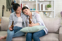 Young Sad Girl Talking With Her Best Friend About Problems. Upset Asian Woman Leaning On Sisters Shoulder Holding Beer Drinking Alcohol To Make Self Better. Lady Hug Consoling For Help And Support