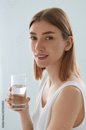 Woman with glass of fresh water in white portrait