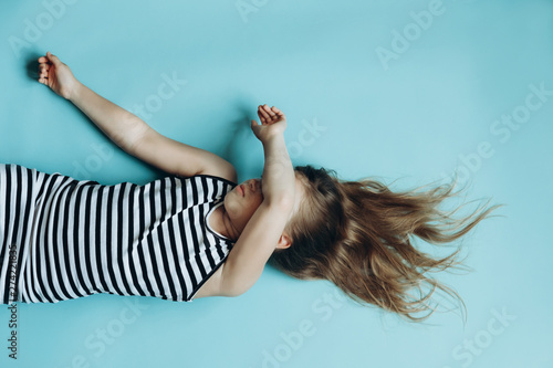Girl laying on blue background covering face. Child sleeping flat lay top view. Having rest, relaxing. Childhood memories. Beautiful flowing hair. Simple minimalist background, wallpaper