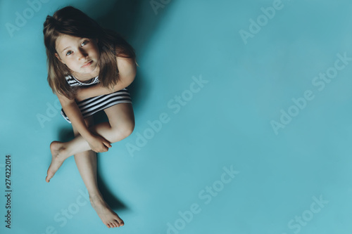 Girl sitting on plain blue background looking at camera Fototapet
