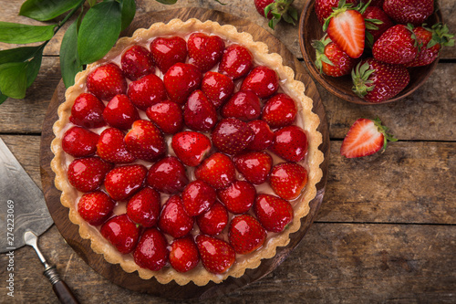 Fotografia delicious strawberry tart on wooden background