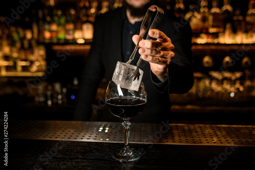 Poster Bar Bartender puts big ice cube in a cocktail