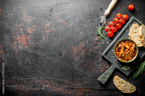 Obraz Sprat in tomato sauce on a cutting Board with tomatoes, bread and rosemary. - fototapety do salonu