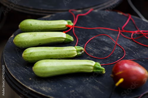 Photo of zucchini, avocado with red wires on black table Wallpaper Mural