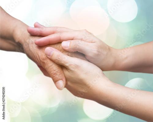 Obraz Caregiver, carer hand holding elder hand in hospice care. Philanthropy kindness to disabled concept. - fototapety do salonu
