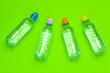 Leinwandbild Motiv plastic water bottles with caps of different colour on the  table