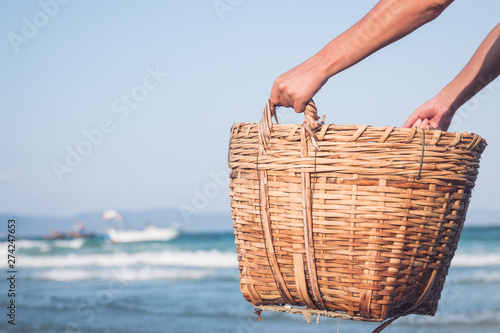 Obraz strong male hands hold a wicker basket on the background of the sea - fototapety do salonu