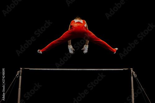 Spoed Fotobehang Gymnastiek horizontal bar gymnastics performing man athlete gymnast on black background