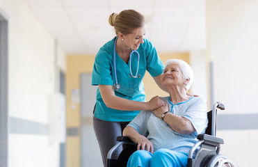 Senior woman in wheelchair with nurse in hospital