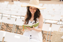 Photo Of Alluring Caucasian Woman Wearing Straw Hat Smiling And Holding Diary Book While Sitting On Chair In Green Park Outdoors