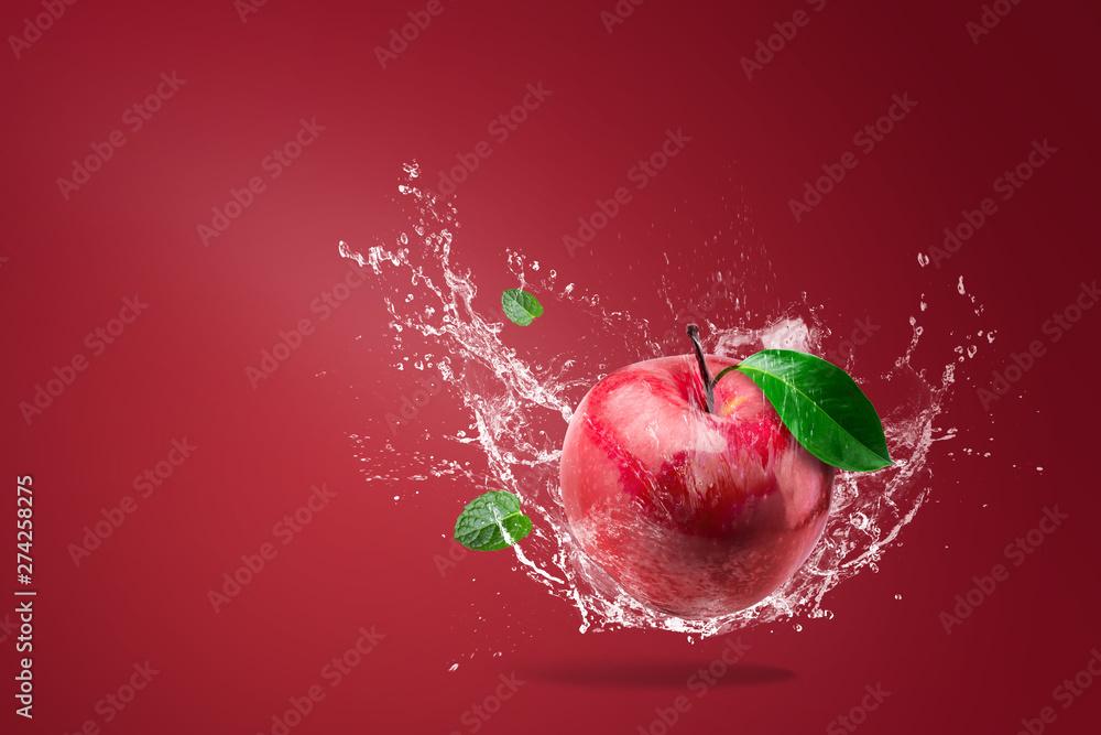 Fototapeta Water splashing on Fresh Red apple on red background