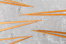 Many Bamboo Chopsticks On Black Cement Stone Background, Top View With Copy Space. A Lot Of Sushi Sticks In The Form Of An Ornament