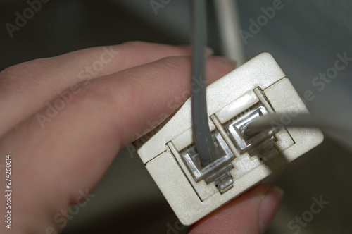 Photo Hand Holding Adsl Filter with Two Telephone Line Entries - 6P4C RJ-11 Connectors