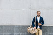 Portrait of bearded businessman wearing eyeglasses holding paper cup and carrying bag
