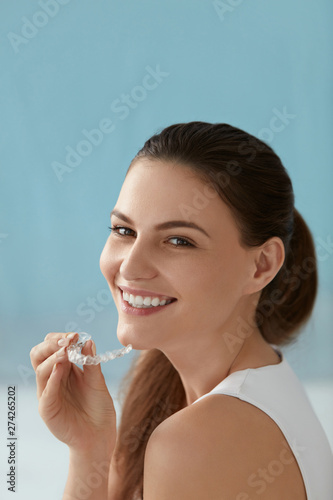 Dental care. Smiling woman with white smile using whitening tray - 274265202