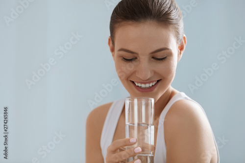 Obraz na płótnie Drink water. Smiling woman holding fresh pure water in glass