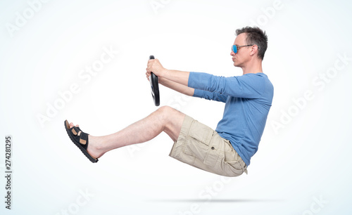Valokuvatapetti Man in sunglasses, shorts, blue t-shirt and sandals drives car with a steering wheel, on light day background