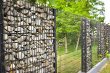 Texture Of Stone Wall. The Fence Made Of Stone. The Stone Wall Is Tied Around With Black Steel Bars. Design Ideas To Make  Backgrounds, Banners And Artwork.