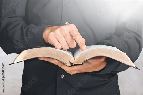Fotografia  Closeup on a Priest Holding a Bible and Pointing Finger