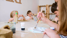 Children Are Sitting At Table In Workshop At Art Lesson And Modeling Workpiece From Wet Clay.