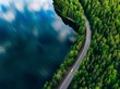 Leinwandbild Motiv Aerial view of road between green forest and blue lake in Finland