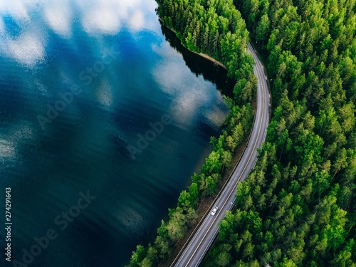Photo sur Aluminium Bleu vert Aerial view of road between green forest and blue lake in Finland
