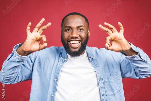 Happy young African-American man isolated against red background Canvas Print