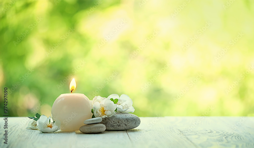 Fototapeta beautiful tender scene with candle, flowers and stones. romantic still life. Relax still life with zen pebble stones, candle. spa wellness tranquil scene, soul equanimity calmnes concept. copy space