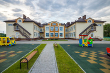 New Modern Two-storied Kindergarten Preschool Building With Big Windows On Green Grassy Lawn And Blue Sky Copy Space Background. Architecture And Development Concept.