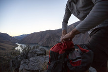A Man Packs Up His Backpack Overlooking The Snake River In Hells Canyon, Idaho.