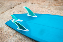 Blue Surfboard Bottom And Fin Detail Against Natural Rock Texture