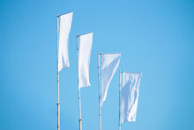 A Lot Of White Flags Against The Blue Sky Hanging On The Mast, Copy Space