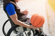 Disabled young basketball player on a wheelchair holding ball and beeing active in sport