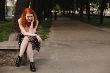 Young Happy Woman Talking On Mobile Phone While Sitting In Park