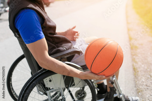 Photo  Disabled young basketball player on a wheelchair holding ball and beeing active