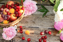 Juicy Black Grapes And Cherries, Pears And Peaches In A Basket In The Garden Close-up And Peonies On A Wooden Old Background, Top View, Copy Space, Selective Focus