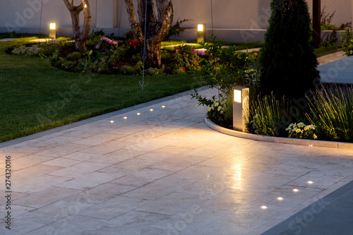 Obraz marble tile playground in the backyard of flowerbeds and lawn with ground lantern and lighting in the warm light at dusk in the evening. - fototapety do salonu